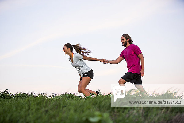 Caucasian woman pulling man on hill