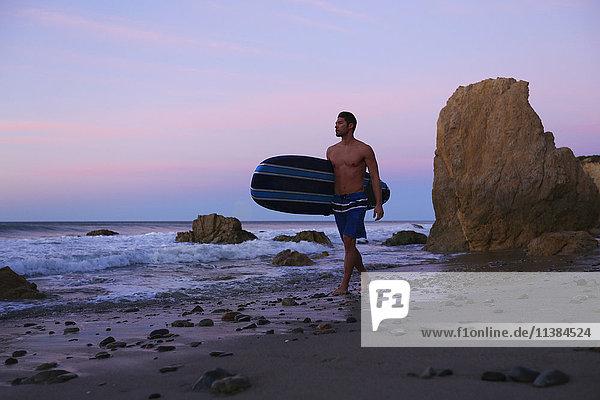 Hispanic man carrying surfboard on beach at sunset
