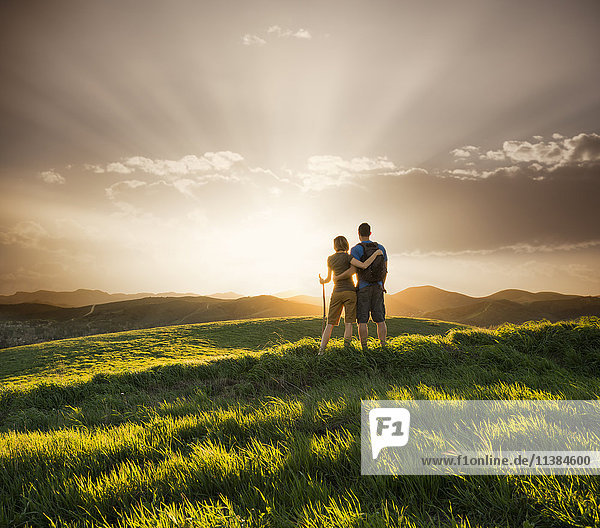 Couple hugging on hill at sunset