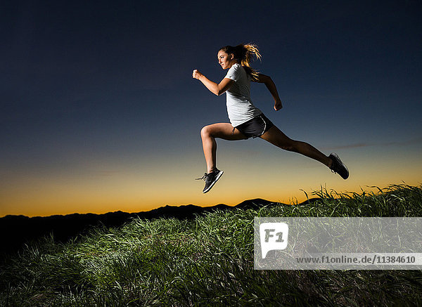 Caucasian woman running at sunset