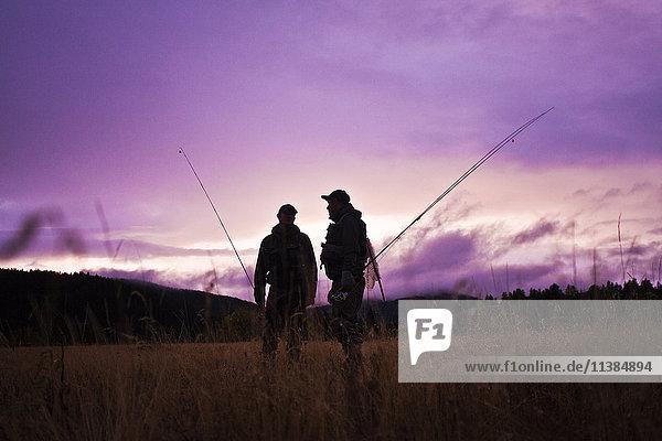 Caucasian men carrying fishing rods