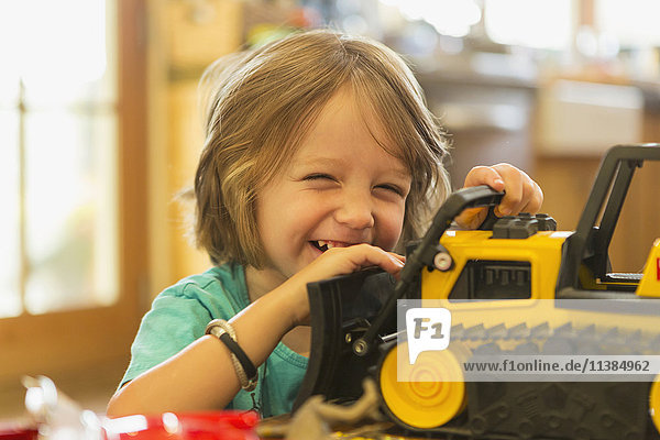 Portrait of Caucasian boy playing with toy bulldozer