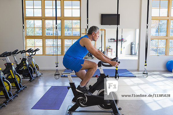 Mixed Race man riding stationary bicycle in gymnasium