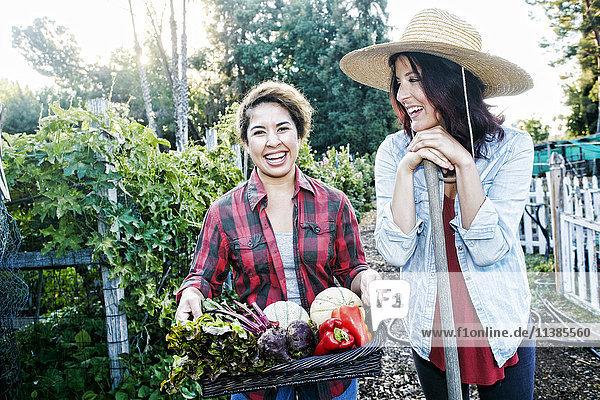 Portrait of women with basket of vegetables in garden Portrait of women with basket of vegetables in garden