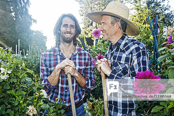 Smiling Caucasian men standing in garden