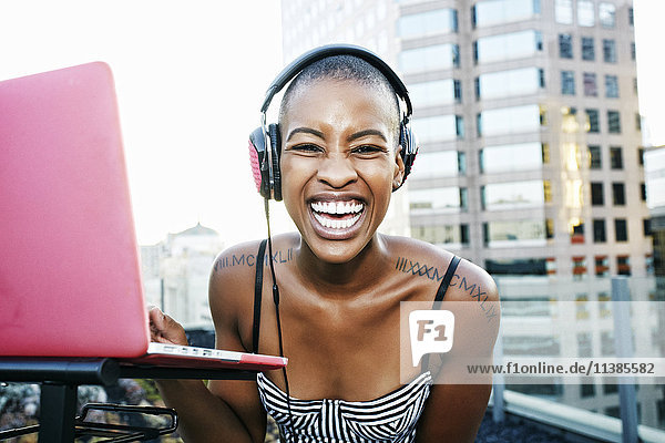Portrait of Black DJ laughing on urban rooftop