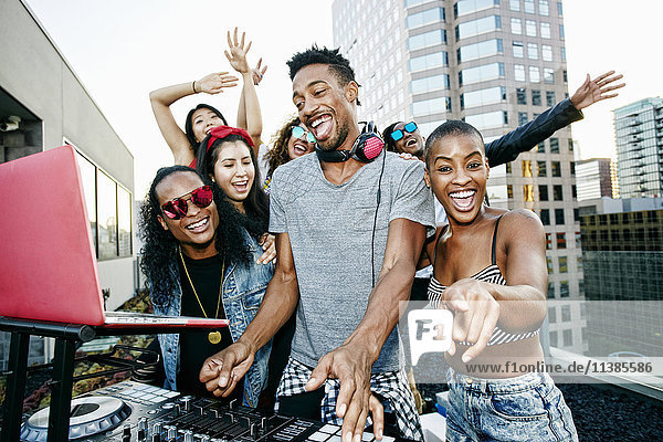 Friends posing with DJ on urban rooftop