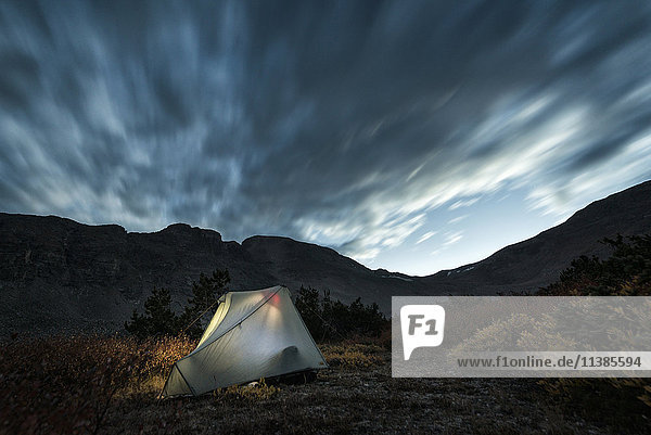 Illuminated camping tent under cloudy sky
