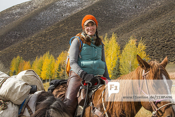 Smiling Caucasian woman riding horse in winter