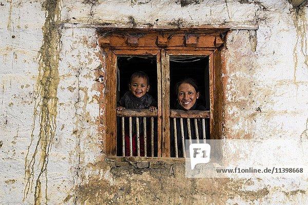 Junge Frau und Sohn schauen aus Fenster des Bauernhof  Purang  Mustang  Nepal  Asien
