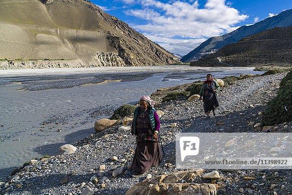 Zwei einheimische Frauen gehen am Fluss  bei Jomsom  Kali Gandaki Tal  Mustang Distrikt  Nepal  Asien