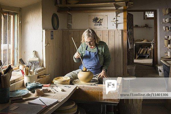 Keramikwerkstatt  Frau bearbeitet Ton mit Schwamm auf Drehscheibe  Pittenhart  Oberbayern  Deutschland  Europa