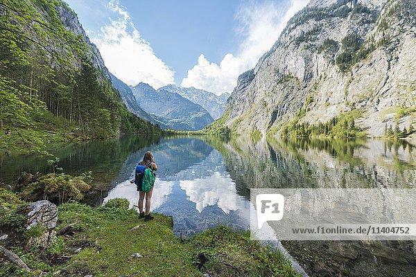 Wanderin steht am Obersee mit Wasserspiegelung  Salet am Königssee  Nationalpark Berchtesgaden  Berchtesgadener Land  Oberbayern  Bayern  Deutschland  Europa