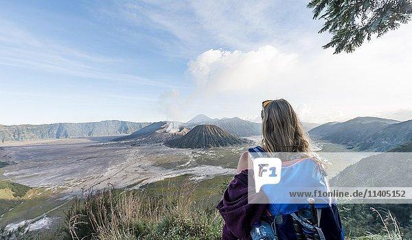 Touristin vor Landschaft  rauchender Vulkan Gunung Bromo  vorne Mt. Batok  hinten Mt. Kursi  Mt. Gunung Semeru  Nationalpark Bromo-Tengger-Semeru  Java  Indonesien  Asien