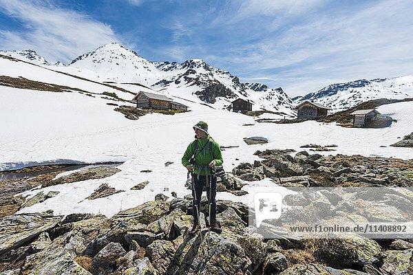 Junger Mann  Wanderer steht vor Hütten  Unterer Giglachsee  Berglandschaft mit Schneeresten  Rohrmoos Obertal  Schladminger Tauern  Schladming  Steiermark  Österreich  Europa