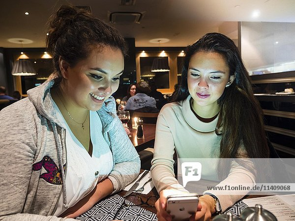 Two young women with mobile phone in a restaurant  London  England  United Kingdom  Europe