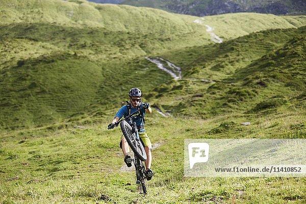 Mountainbiker fährt einen Trail in hügeliger Landschaft  Kalkkögel  Tirol  Österreich  Europa