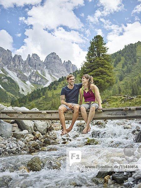 Junges Pärchen sitz auf einer Brücke  Kemater Alm  Tirol  Österreich  Europa