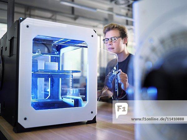 Angestellter  25-30 Jahre  öffnet einen 3D Drucker in einem Fabrikationslabor  FabLab  Wattens  Tirol  Österreich  Europa Angestellter, 25-30 Jahre, öffnet einen 3D Drucker in einem Fabrikationslabor, FabLab, Wattens, Tirol, Österreich, Europa