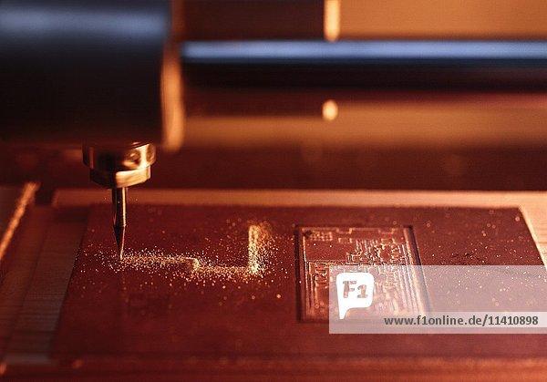 CNC Maschine fräst Leiterbahnen für eine Elektronische Schaltung in eine Kupferplatine