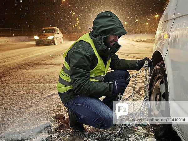 Mann mit Warnweste beim Anlegen der Schneeketten an verschneiter Landstraße  Wattens  Tirol  Österreich  Europa