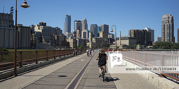 'Cyclists and pedestrians on a bridge with a view of the skyline of Minneapolis; Minneapolis  Minnesota  United States of America'
