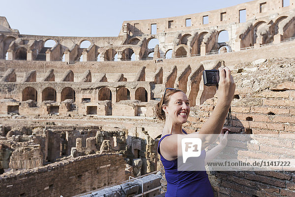 'A young female tourist takes a selfie with her camera at the Roman Colosseum; Rome  Italy'