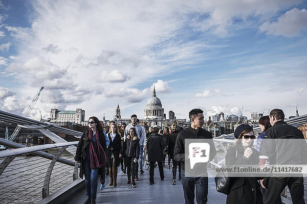 'Pedestrians walking across Millennium Bridge with St Paul's Cathedral in the distance; London  England'