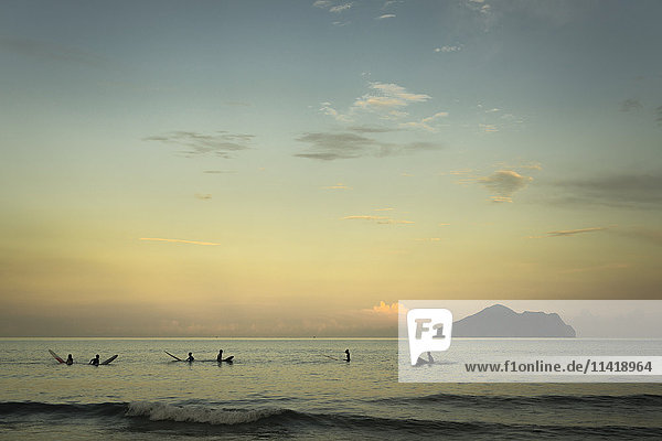 'Surfers waiting for waves and Turtle island behind them at sunset  Waiao beach  Yilan County; Taiwan  China'