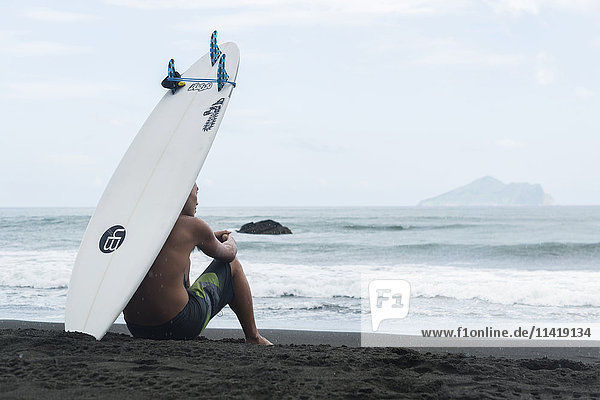 'A surfer sits on the shore as he waits to get into the sea  Waiao beach  Yilan County; Taiwan  China'