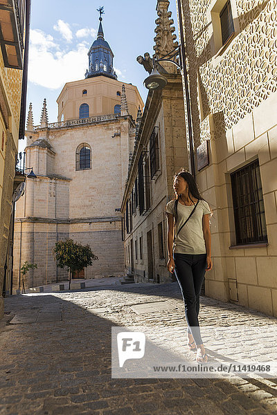 'Asian girl walking along the street with Segovia's Cathedral as background; Castilla Leon  Spain'