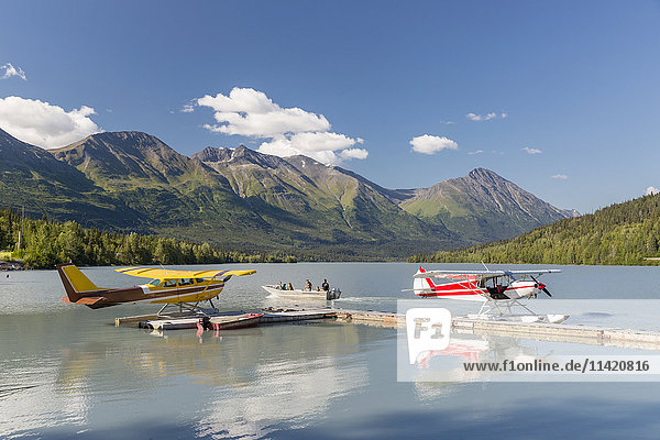 Two float planes docked at the Trail Lake Float Plane Base on a clear Day  the Kenai Mountains in the background  Kenai Penninsula  Southcentral Alaska  USA  Summer