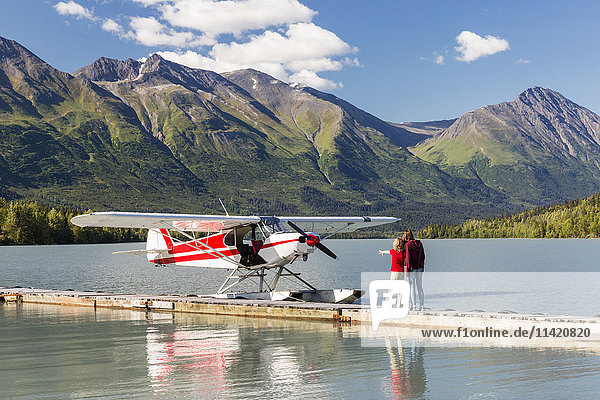 A Mother with her daughter looking at a float plane docked at the Trail Lake Float Plane Base on a clear day  the Kenai Mountains in the background  Kenai Peninsula  Southcentral Alaska  USA  Summer