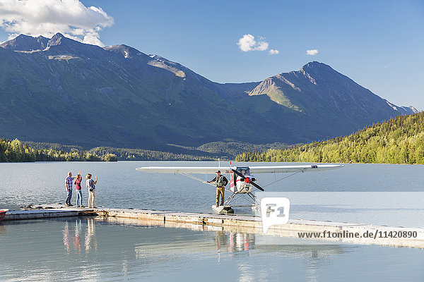 Visitors wave to the pilot standing on a Super Cub float plane  Trail Lake Float Plane Base  Moose Pass  Kenai Peninsula  Southcentral Alaska  USA