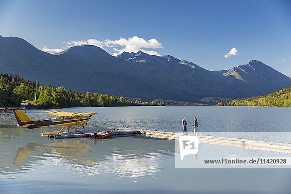 A woman and a man stand on a dock where a float plane is docked  Trail Lake Float Plane Base  Moose Pass  Kenai Peninsula  Southcentral Alaska  USA