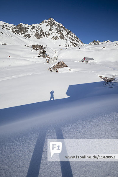 'Photographer Doug Lindstrand takes a picture of his shadow in Hatcher Pass  near Independence Mine in late winter. The old delapidated mine buildings show in the snow in the background  near Palmer  South-central Alaska; Alaska  United States of America'