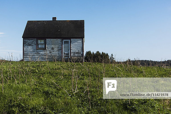 'Small weathered wooden house surrounded by grass on Cape Breton Island; Nova Scotia  Canada'