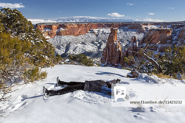 'A woman makes a snow angel in the snow in front of the 450 foot high sandstone Independence Monument in the Colorado National Monument; Colorado  United States of America'