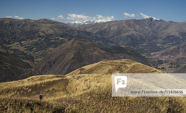 'A hiker makes his way through the foothills of the Andes Mountains with the snowcapped peaks in the background of the Peruvian landscape; Cusco  Peru'
