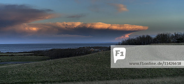 'Dramatic cloud formation glowing pink at sunset over the ocean with green fields in the foreground; South Shields  Tyne and Wear  England'