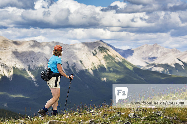 'Female hiker walking along a rocky hill overlooking mountain range and valley with a cloudy sky  West of Bragg Creek; Alberta  Canada'