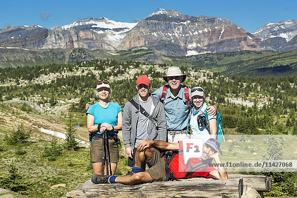'Group of hikers posing on a log bench with valley below and mountains and blue sky in the distance; Banff  Alberta  Canada'