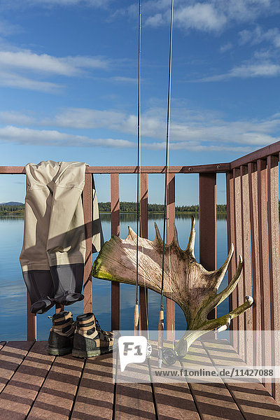 'Fly fishing poles  boots  and waders rest against a railing with a shed moose antler on the deck of a building at the Tikchik Narrows Lodge  Tikchik Lake in the background on a clear summer day  Wood Tikchik State Park  Southwestern Alaska; Alaska  United States of America'