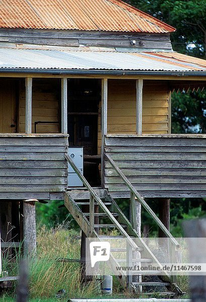 Dilapidated Queenslander style house detail of front steps  weatherboards and rusted corrugated iron roof. Calliope  Queensland  Australia. (Photo by: Auscape/UIG)