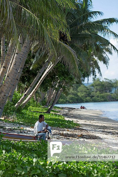 A man on a beach under palm trees at the village of Salgliat Dol  Yamdena island  Tanimbar Islands  Maluku Province  Indonesia. (Photo by: Auscape/UIG)