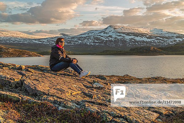 Woman with sunglasses and sneakers  sitting on a rock at sunset with mountains with snow and a lake in the background  Stora sjöfallets national park  Gällivare  Swedish Lapland  Sweden.