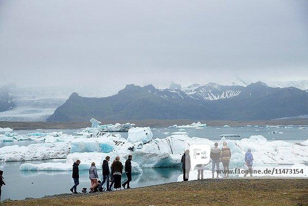 Tourists at Jokulsarlon glacier lake in Iceland