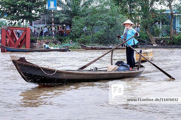 Woman rowing sampan boats on the Mekong River in Cai Be  Mekong Delta  Vietnam  Asia.