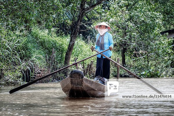 Woman rowing a sampan boat on the Mekong River in Cai Be  Mekong Delta  Vietnam  Asia.