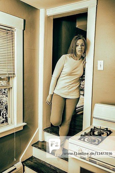 Young woman standing in her kitchen doorway.